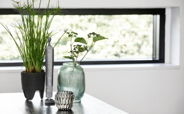 Unterschiedliche Living Produkte wie z.B. die Grüne Stria Vase und eine Abena Figur