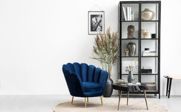 Deep blue coloured velour chair and a black cabinet