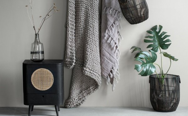 Black cabinet and a basket with artificial plant