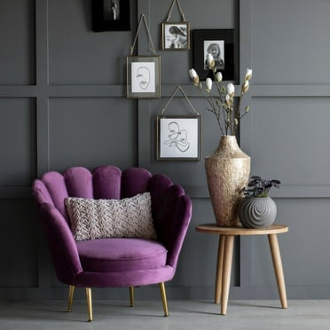 Purple coloured velour chair next to a wood side table with grey flowerpot