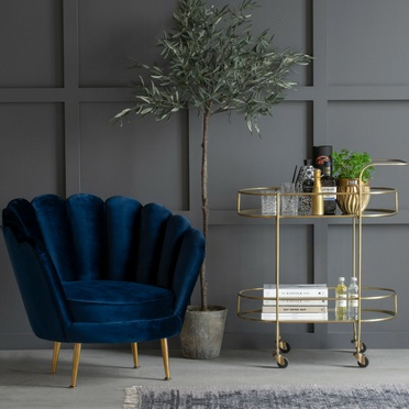 Deep blue coloured velour chair and a golden trolley table
