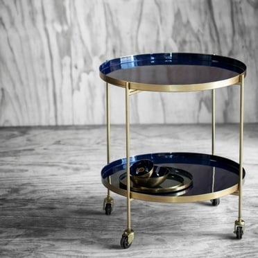 Blue and gold trolley table in front of grey wall