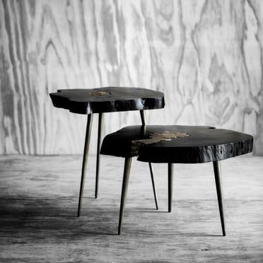 Two black and gold wooden side tables in front of grey wall