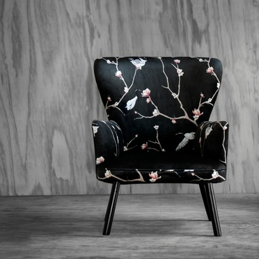 Black chair with flower pattern in front of grey wall