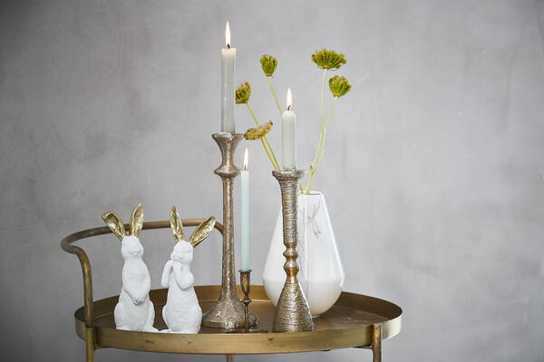 Easter decoration and candlesticks on golden trolley