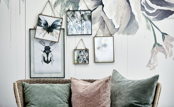picture frames with leaves and brown sofa with green and red cushions