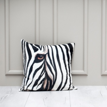 A cushion with zebra pattern in front of grey wall