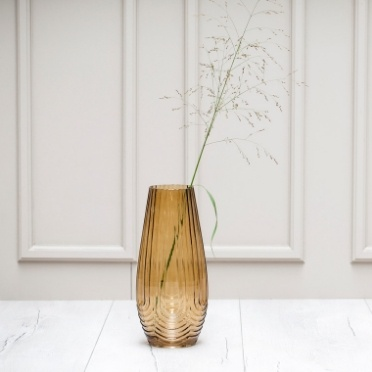 Brown glass vase standing next to grey wall