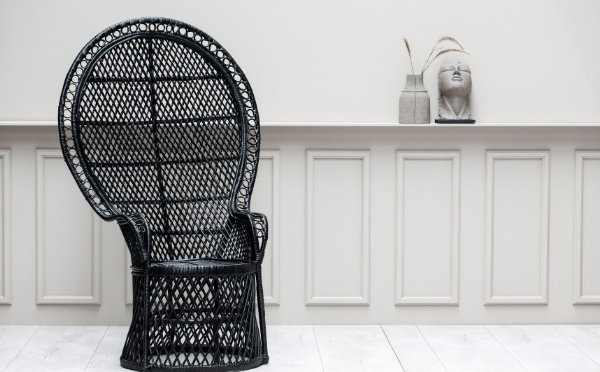 Black peacock chair standing next to at grey wall