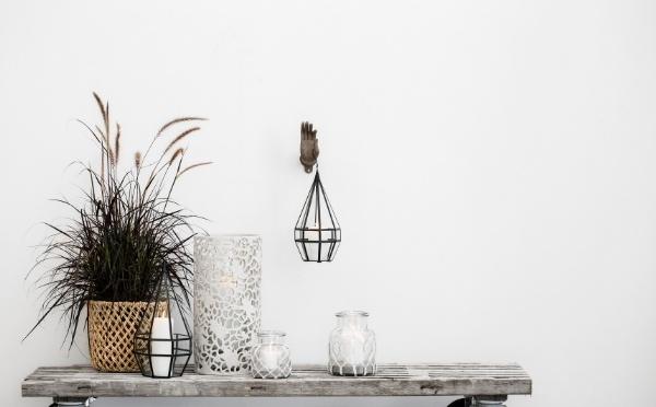 Unterschiedliche Laternen und einen Korb mit einem Pflanze auf einer Bank.