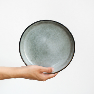 Hand holding grey plate in front of white wall