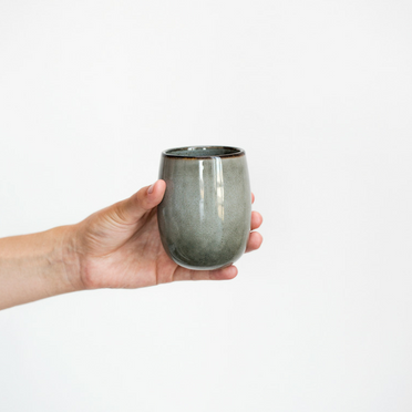 Hand holding a grey mug in front of white wall