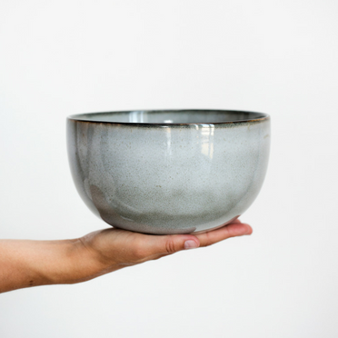 hand holding a grey bowl in front of white wall