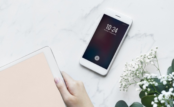 Hands holding an iPad, iPhone on the table and white flowers