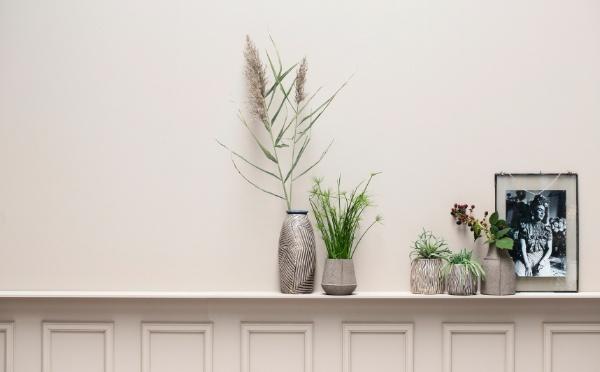 Lene Bjerre Vasen auf einem Regal mit grünen Pflanzen