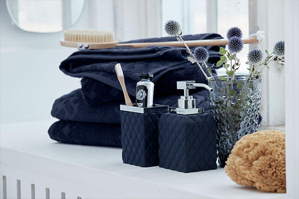 Timeless and classic black bathroom accessories consisting of a soap dispenser and towel