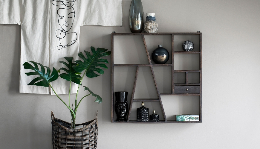 A brown shelf on a grey wall with a green plant next to it.