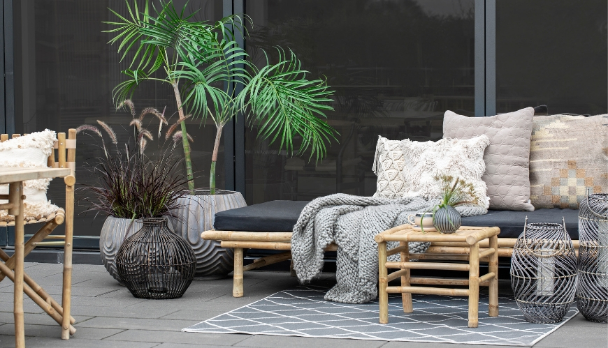 Bamboo daybed with black mattress and sandy brown cushions and a green plant next to it.