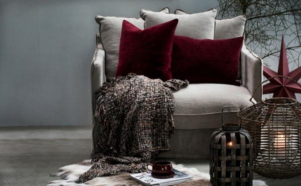 Chaise avec des coussins rouges et une couverture cozy