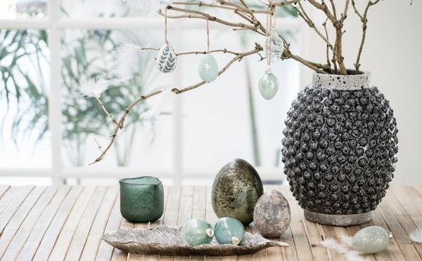Ostereier in Pastellfarben, rustikale Vase und Teelicht