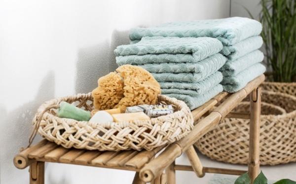 Mandisa Bank mit Handtüchern und einem Korb mit Badzubehör