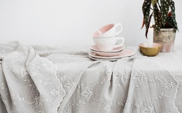 Tisch mit einer Tischdecke, Tellern und Tassen