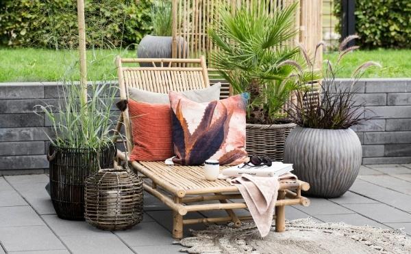 Bambus Sonnenbett mit roten Kissen und Blumentöpfe daneben.