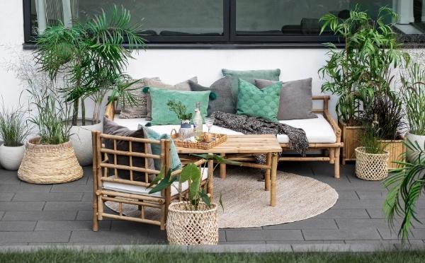 Bambus Möbel auf einer Terrasse und Korben und Blumentöpfe mit Pflanzen drin.