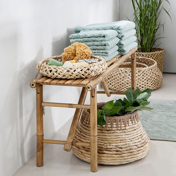 Bamboo bench on a bathroom with abaca handwoven baskets from wholesaler Lene Bjerre