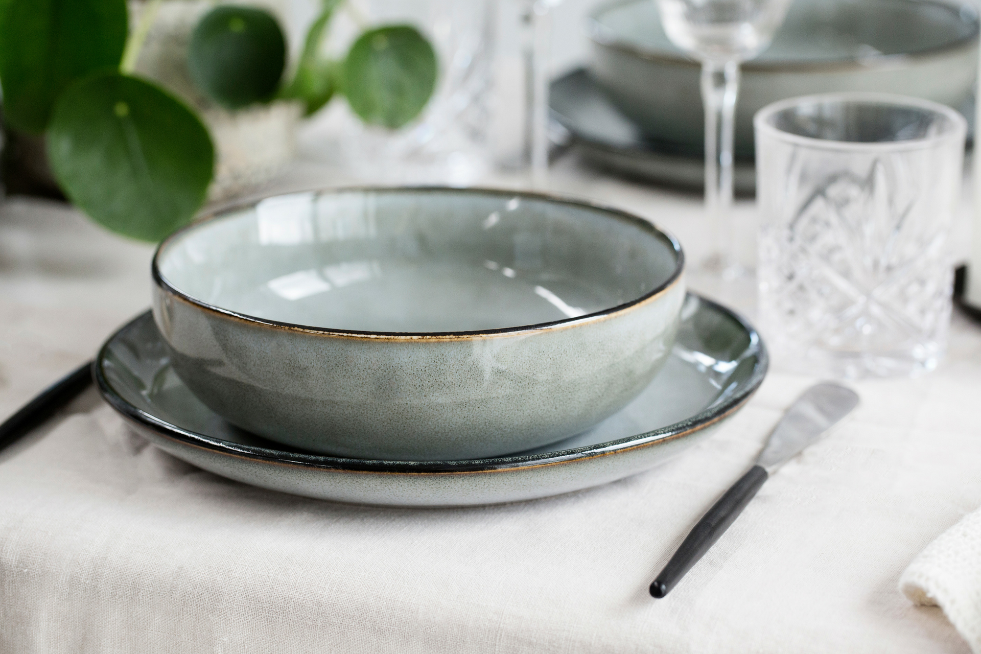 Table setting with grey bowl, plate and crystal glass
