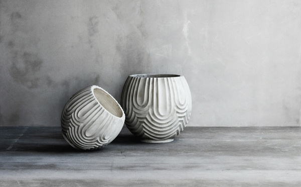 Two white flowers pots and a grey wall