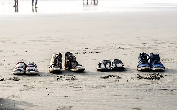 Four pairs of shoes on a beach
