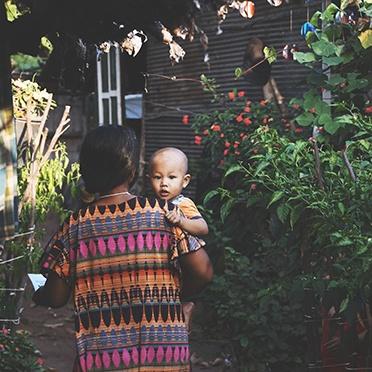 Une maman qui porte un robe colorée tenant son enfant dans les bras hors du soleil