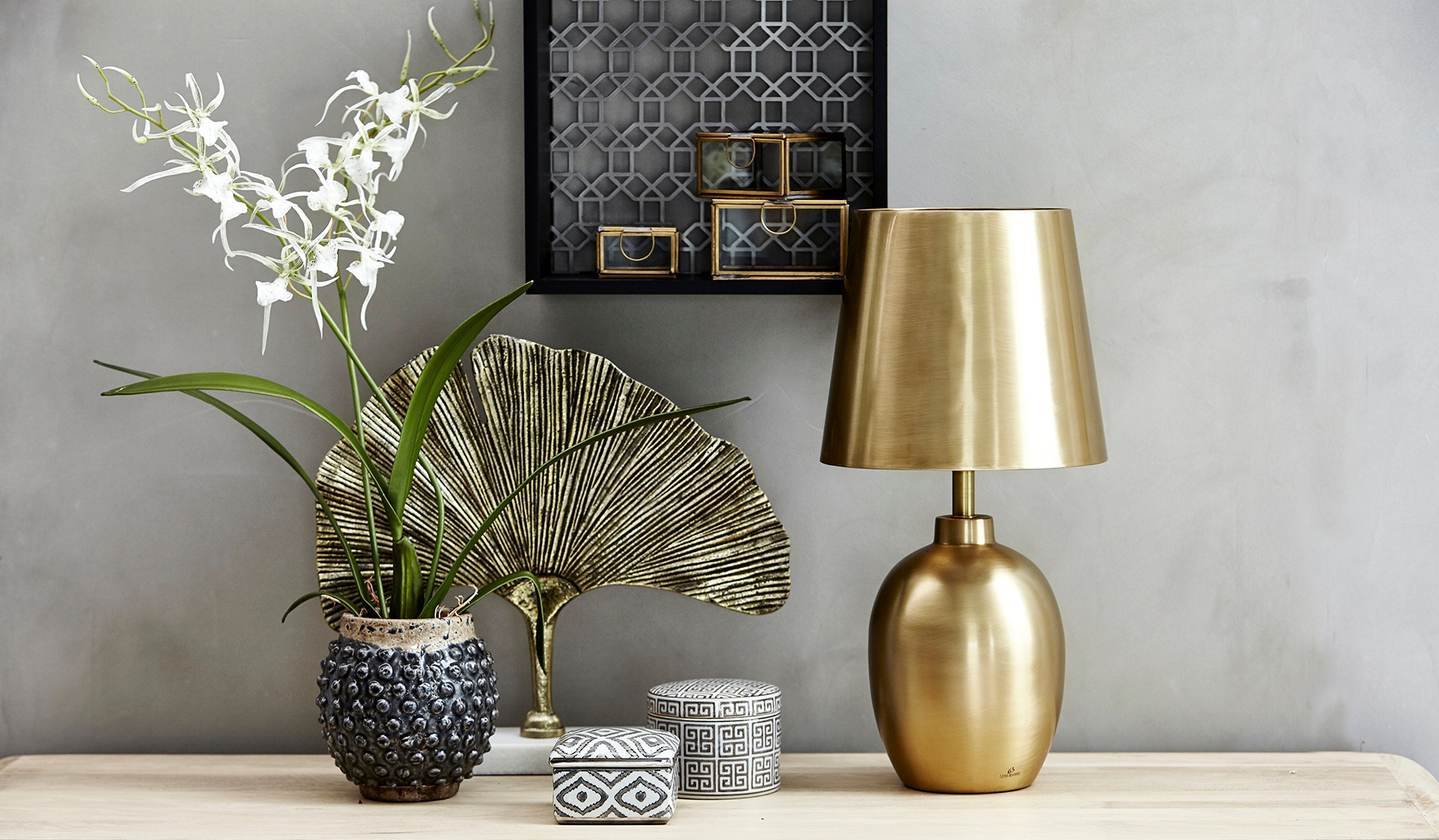 Flower pot in table with a gold lamp and small boxes