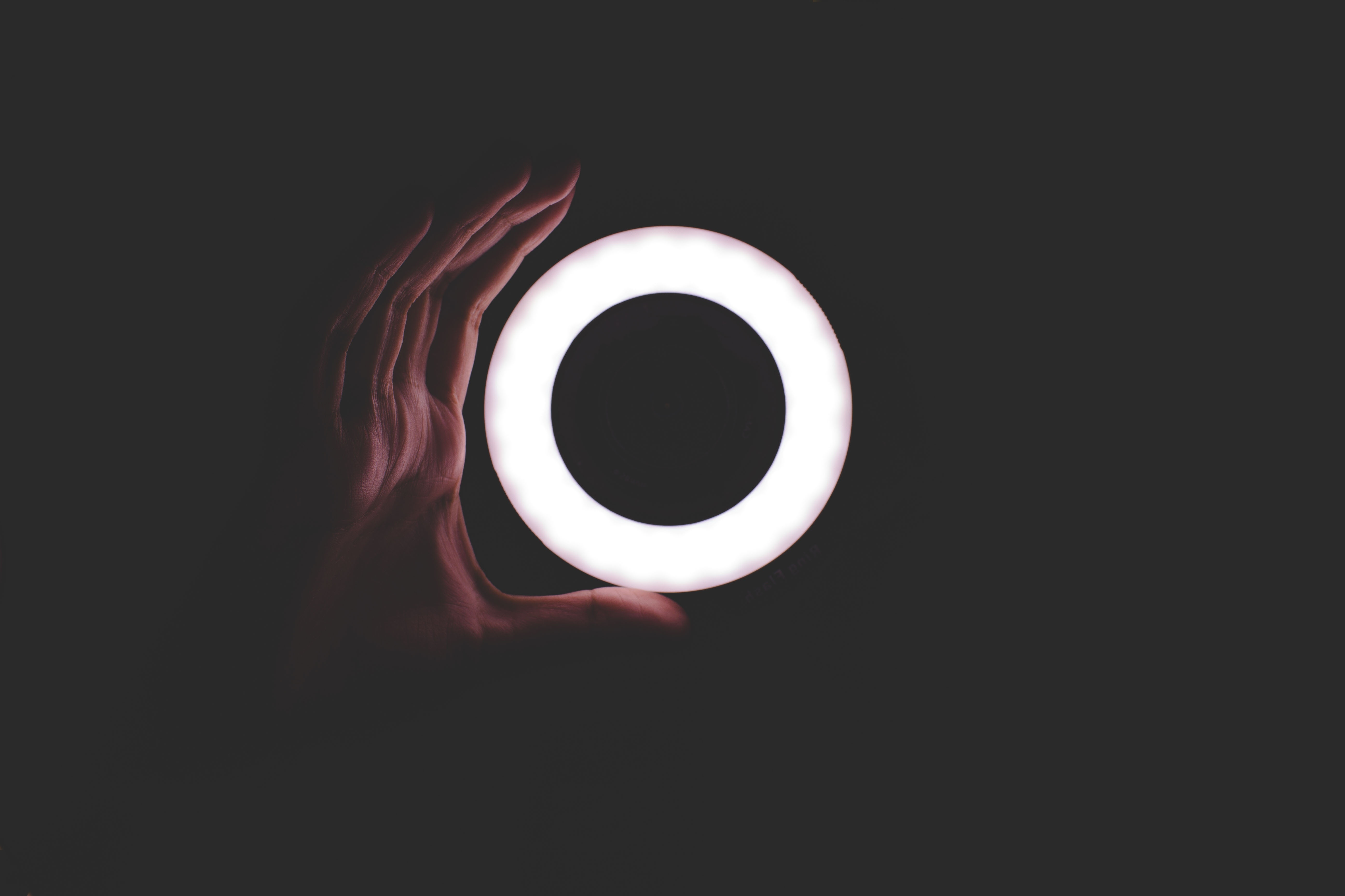 Hand holding a circle of light with dark background